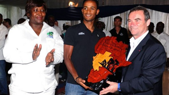 Eritrea's Natnael Berhane (C) receives the African Cyclist of the year 2012 trophy from Bernard Hinault (R), five-times Tour de France champion, at the Beach Club in Libreville, on January 20, 2013. Berhane is only one of several Eritreans in this cycling-mad Horn of Africa state making his mark on the sport. (AFP/File)