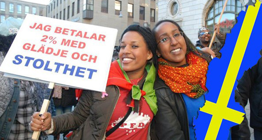 """Swedish-Eritrean citizens holding a sign that reads """"I pay 2% with joy and Pride"""""""