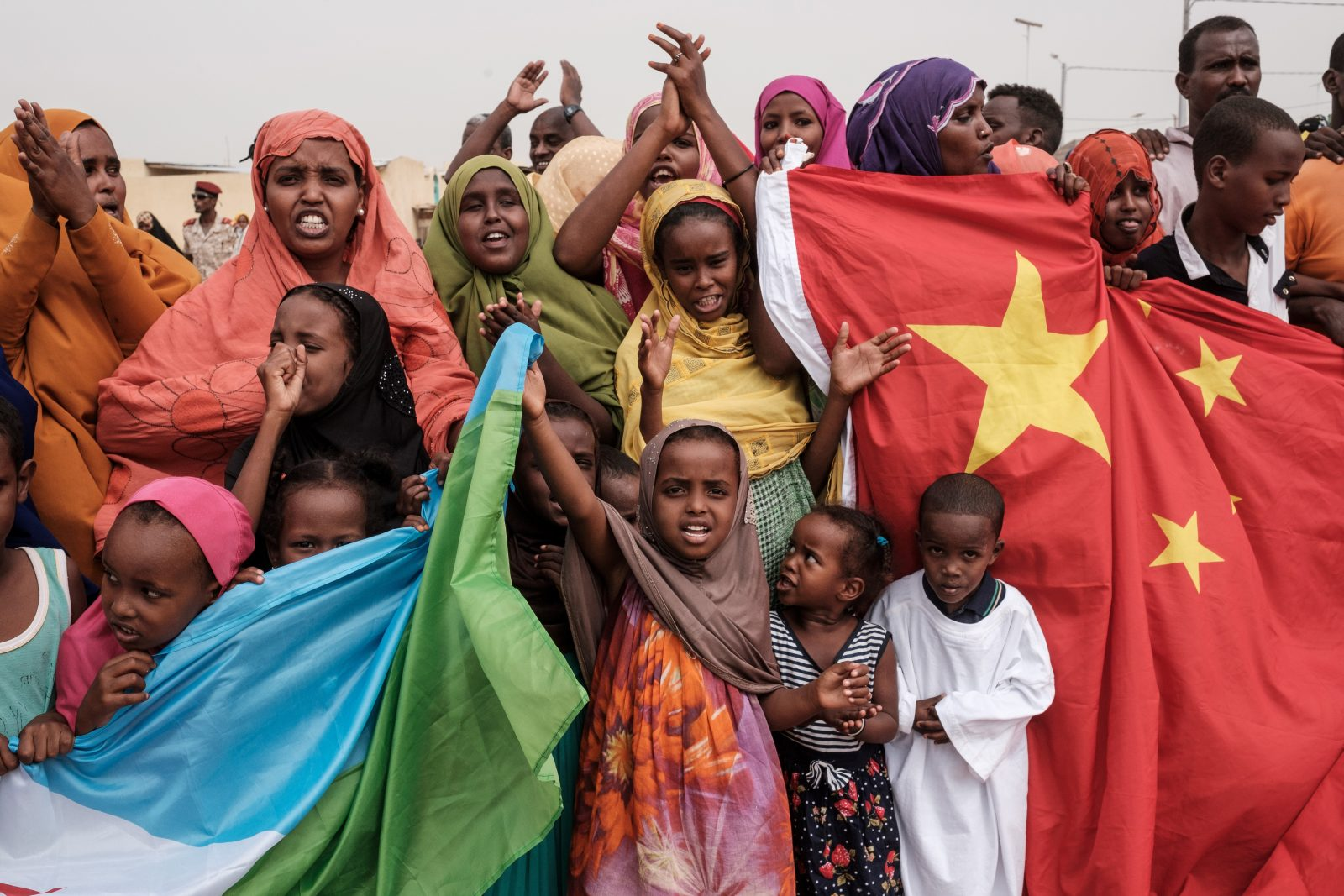 Locals hold Chinese and Djiboutian national flags